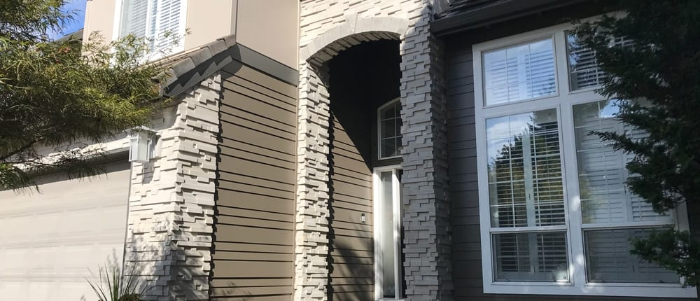 stone brick entryway with white stone accent on garage